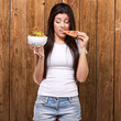 portrait of young woman eating pizza and looking salad against a