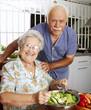 Señores abuelos cocinando en una cocina.Comiendo ensalada.