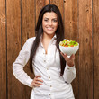 portrait of young woman holding salad against a wooden wall