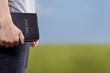 Standing Holding the Bible in a Field - 41217218