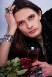 beautiful man with a glass of cognac and roses