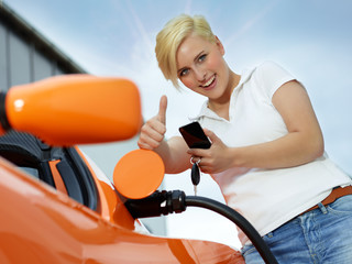 Woman with cellphone loading electrically powered car
