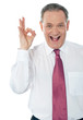 Happy satisfied businessman with okay hand sign