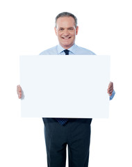 Handsome man holding blank white billboard