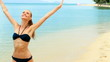 Happy woman walking on the exotic beach in the summertime