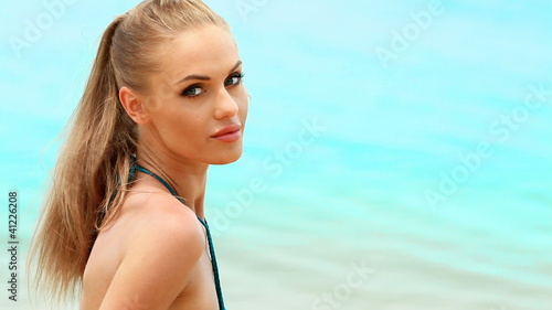 Portrait of cute woman relaxing on the tropical beach at summer