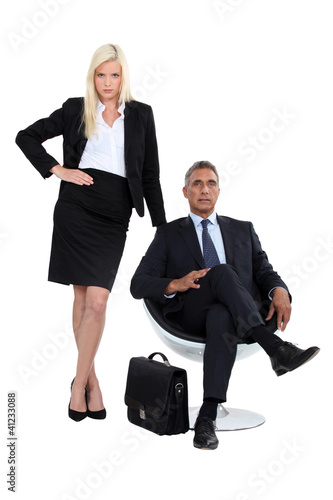 Businessman sitting in a chair next to his glamourous assistant