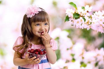 little girl with cherry berries bowl in garden
