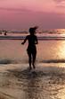 Silhouette of  girl  running across  ocean at sunset