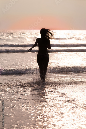 Silhouette of the girl  running across the ocean at sunset
