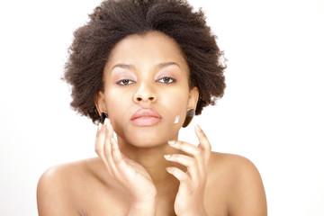 Lovely ethnic woman applying face cream or moisturizer