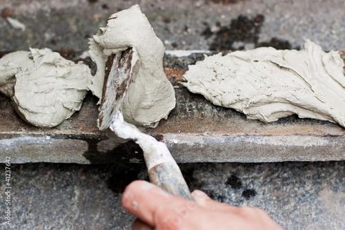Handwerker trägt Kleber auf Stellstufe auf