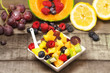 greedy fruit salad with red fruits on wood