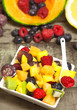 delicious fruit salad with red fruits in a ceramic bowl