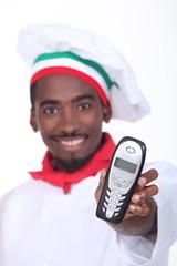 A black chef handing a phone.