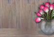 Pink tulip and willow branches on wood texture
