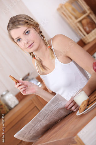 Girl reading newspaper whilst eating breakfast