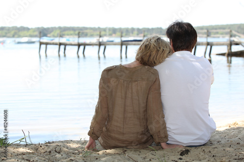 Couple sitting lakeside