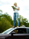 Woman on top of her car in field looking at map