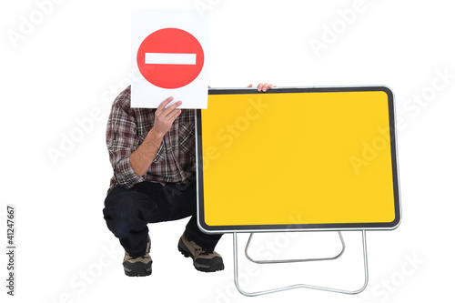 Worker with blank road sign