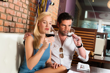 Ein attraktives Paar trinkt Rotwein in einem Restaurant