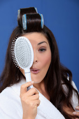 Funny woman with hair rollers and brush