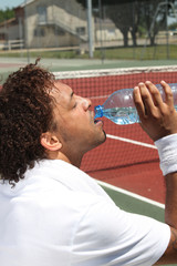 male tennis player drinking water