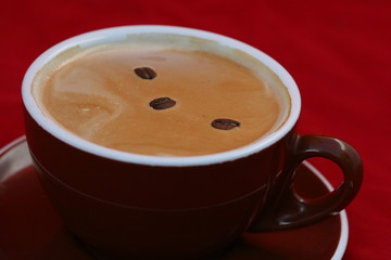 Coffee beans swims on cappuccino surface in cup