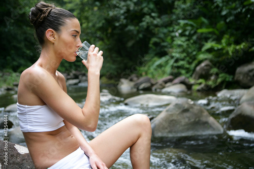 Brunette drinking mineral water straight from stream