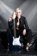 Junge blonde Frau mit E Gitarre auf der Couch