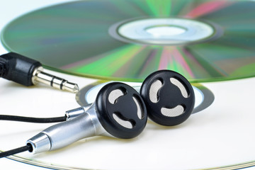 A set of headphones lying on a music cd