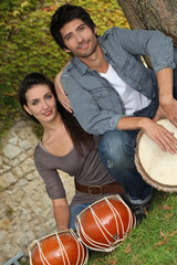 Couple playing the drums outside