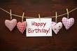 4 Stoffherzen mit Happy Birthday auf Holzbrett