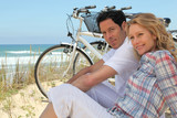 Couple with bikes sitting on the sand dunes