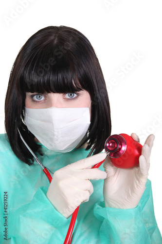 Doctor listening to a plastic heart with a stethoscope