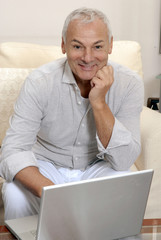 Un señor utilizando un ordenador,computador en casa.