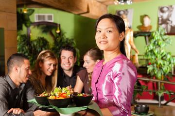 Junge Leute mit Bedienung essen in einem Thai Restaurant