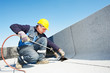 Leinwanddruck Bild - Flat roof covering works with roofing felt