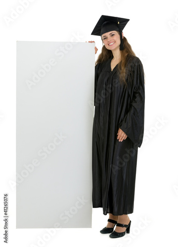 Happy graduation student holding blank billboard