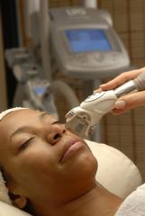 Mujer morena aplicando láser facial en un spa.Tratamiento facial
