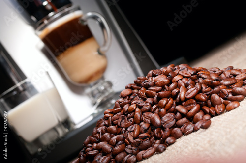 Coffee beans heap, latte and coffee machine