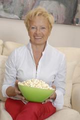 Señora sentada en un sofá comiendo palomitas de maíz.