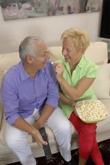 Pareja adulta viendo televisión comiendo palomitas de maíz.