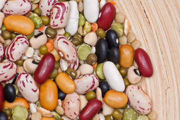 Legumes and cereales close up in wooden plate