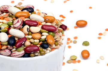 Legumes and cereales close up in white cup isolated