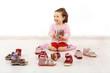 Leinwanddruck Bild - Kleinkind freut sich über ein Paar Schuhe