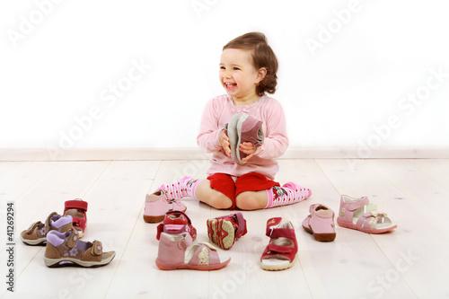 Leinwanddruck Bild Kleinkind freut sich über ein Paar Schuhe