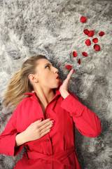 Woman with red coat blowing rose petals