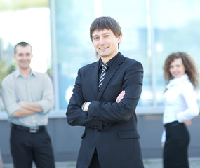 Male Business leader standing in front of his team