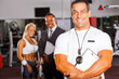 muscular gym trainer portrait with colleagues